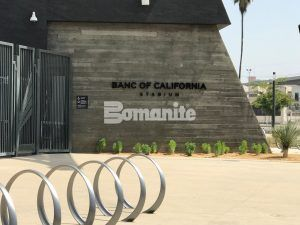 Metal Bike Racks are in decorative concrete that is a Bomanite Sandscape Texture Walkway faced by a Cast in Place Wood Textured Wall.
