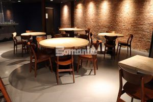 Round tables in a communal seating area, among other seating choices, are enhanced by the Bomanite Micro Top decorative concrete flooring installed by Musselman and Hall at Elmwood in Maplewood, MO.