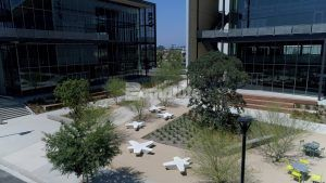 Courtyard view of Flight at Tustin Legacy creating living working office environment with Bomanite Revealed Exposed Aggregate landscaped pedestrian walkways, courtyards and outdoor work spaces in Tustin, CA, installed by Bomel Construction.