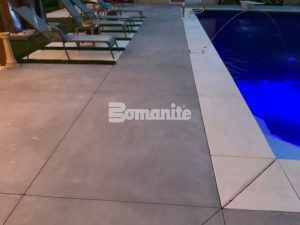 Close up view of the concrete decking and pool edge of backyard retreat transformation using Bomanite Revealed Exposed Aggregate System and installed by Concrete Arts, Inc.