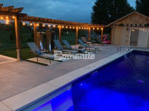 Wider view of concrete pool deck, lounge chairs, pergola, and cabana of stunning backyard retreat transformation using Bomanite Revealed Exposed Aggregate System and installed by Concrete Arts, Inc.