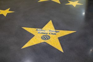 Donor star in decorative concrete floor created with Bomanite Modena TG system with a sleek dark Bomanite Renaissance Polished Concrete Floor as the background at the Jaffrey Park Theatre in Jaffrey, NH, installed by Bomanite Licensee Premier Concrete Construction.