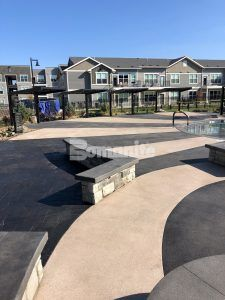Another view pool deck and cabana area at Icon Apartment Homes at Ferguson Farm in Bozeman, MT, installed by Bomanite licensee Architectural Concrete & Design using Bomanite Exposed Aggregate Systems with Bomanite Sandscape Texture and Bomanite Revealed.